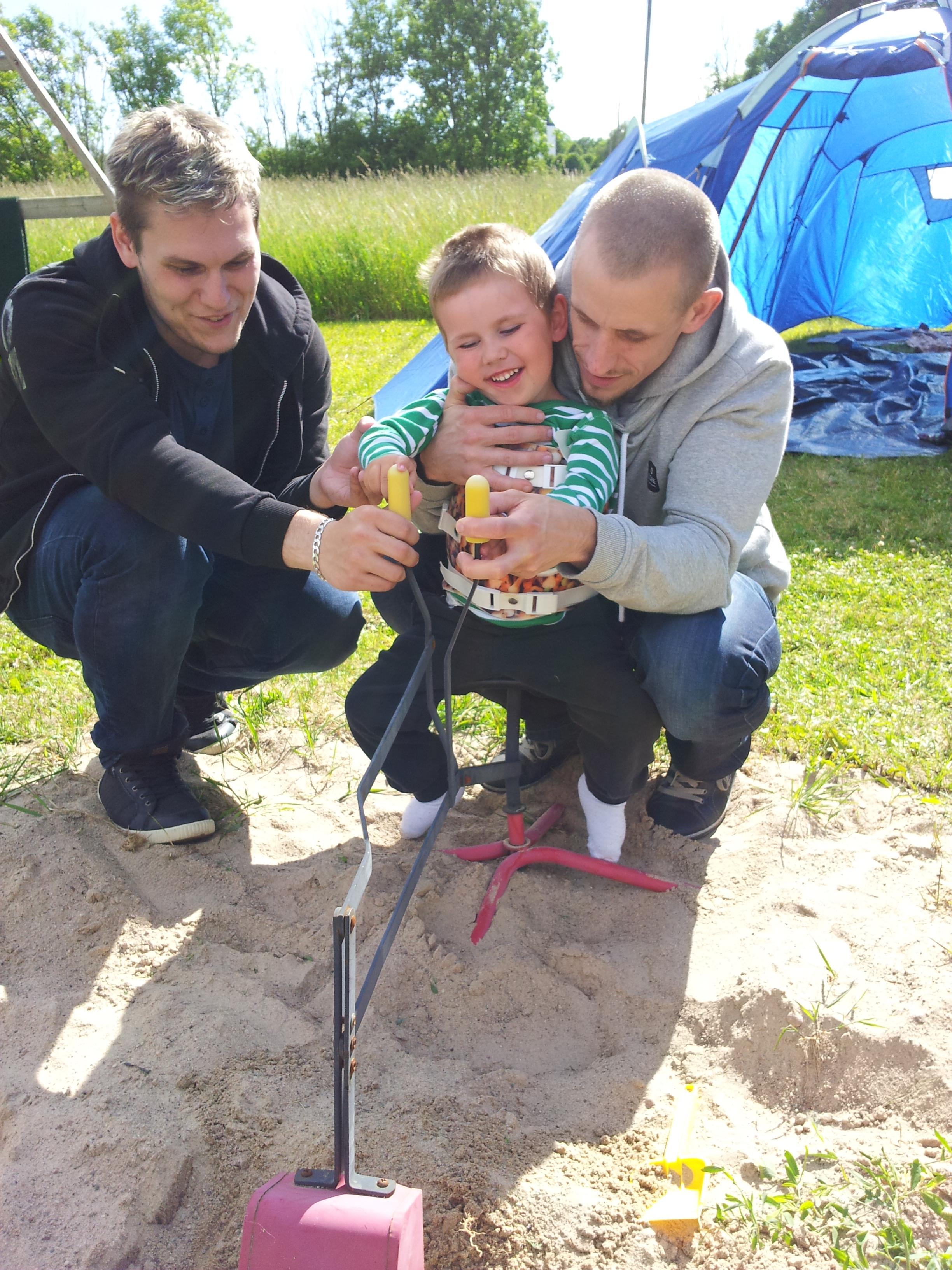 Här ärOskar med sin pappa och en assistent som hjälper honom att sitta på en grävmaskin i en sandhög. Pappa håller upp kropp och huvud, medan assistent Danne sköter spakarna med Oskars händer.
